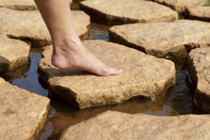Woman stepping on stone in middle of stream